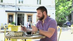 Man som bläddrar smartphonen under frukosten i kafé lager videofilmer