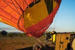 Man som blåser upp luftballongen med varm luft från skottlossningdysa Royaltyfri Bild