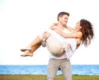Man som bär hans flickvän i en blåsig strand Royaltyfria Bilder