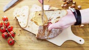 Man som breder smör på bröd med jordnötsmör Royaltyfria Bilder