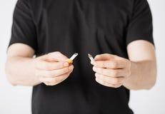 Man som bryter cigaretten med händer Arkivfoton