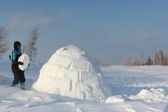 Man som bygger en igloo i en häftig snöstorm arkivfoton