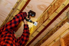 Man som bygger en träuteplats med att bulta skruva tillsammans strålar arkivbild