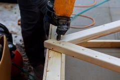 Man som bygger en tr?uteplats med att bulta skruva tillsammans str?lar arkivfoto