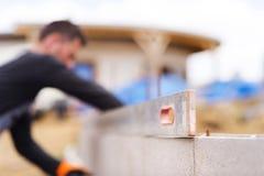 Man som bygger ett hus Arkivfoto