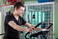 Man som cyklar på motionscykelen Arkivfoton