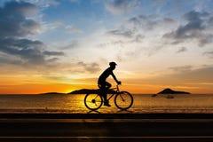 Man som cyklar på stranden Royaltyfria Bilder