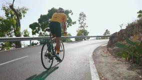 Man som cyklar på utomhus- övning för vägcykel på en tom väg i morgonen Extremt sportbegrepp långsam rörelse arkivfilmer