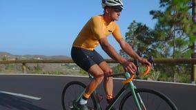 Man som cyklar på utomhus- övning för vägcykel på en tom väg i morgonen Extremt sportbegrepp långsam rörelse lager videofilmer