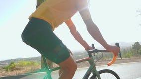 Man som cyklar på utomhus- övning för vägcykel på en tom väg i morgonen Extremt sportbegrepp närbild som är långsam arkivfilmer