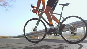 Man som cyklar på utomhus- övning för vägcykel på en tom väg i morgonen Extremt sportbegrepp närbild som är långsam lager videofilmer