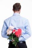 Man som döljer en blomma bak hans baksida. Royaltyfria Bilder