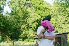 Man som döljer hans framsida med pionbukettträdgården Royaltyfri Fotografi
