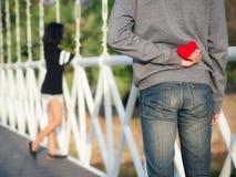 Man som döljer röd hjärta bak hans baksida för hans flickvän Förälskelse valentindagbegrepp royaltyfri foto