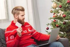 Man som direktanslutet shoppar på jul arkivbilder