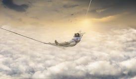 Man som drömmer, i att vagga netto ovanför himmel royaltyfria bilder