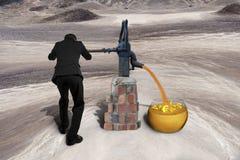 Man som drar den guld- öknen för pump för sandvalutasymboler retro Royaltyfri Foto