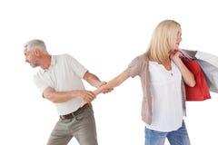 Man som drar kvinnas hand, som hon bär shoppingpåsar Arkivfoto