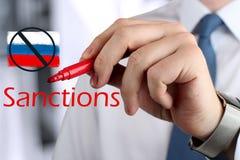 Man som drar sanktioner för ett ord vid en röd penna Fotografering för Bildbyråer