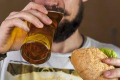 Man som dricker öl och äter hotdogen royaltyfria foton