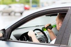 Man som dricker alkohol, medan köra bilen Arkivbild