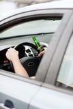 Man som dricker alkohol, medan köra bilen Fotografering för Bildbyråer