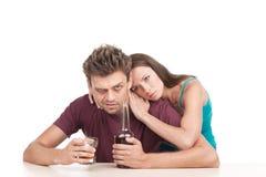 Man som dricker alkohol och kvinnan som tröstar honom Arkivfoton
