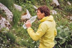Man som dricker den hållande plast- flaskan för kallt vatten i berg Royaltyfria Foton