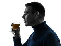 Man som dricker den orange fruktsaftsilhouetteståenden Arkivbilder