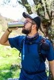 Man som dricker från en isolerad flaska royaltyfri bild