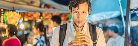 Man som dricker fruktsaft för sockerrotting på det asiatiska marknadsBANRET, LÅNGT FORMAT arkivfoton