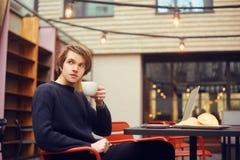 Man som dricker kaffe i en restaurang på terrassen Freelanceren som är utomhus- med en bärbar dator, har frukosten med giffel Bar royaltyfri foto