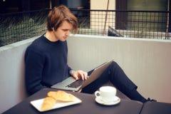 Man som dricker kaffe i en restaurang på terrassen Freelanceren som är utomhus- med en bärbar dator, har frukosten med giffel Bar fotografering för bildbyråer