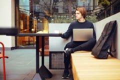 Man som dricker kaffe i en restaurang på terrassen Freelanceren som är utomhus- med en bärbar dator, har frukosten med giffel Bar arkivbild
