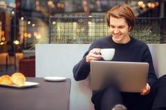 Man som dricker kaffe i en restaurang på terrassen Freelanceren som är utomhus- med en bärbar dator, har frukosten med giffel Bar royaltyfri bild