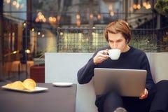 Man som dricker kaffe i en restaurang på terrassen Freelanceren som är utomhus- med en bärbar dator, har frukosten med giffel Bar arkivfoton