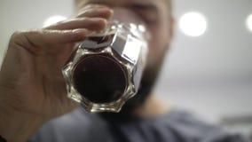 Man som dricker kaffe med ett genomskinligt exponeringsglas stock video