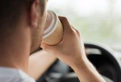 Man som dricker kaffe, medan köra bilen Arkivfoton