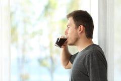 Man som dricker kaffe som ser till och med fönster Fotografering för Bildbyråer