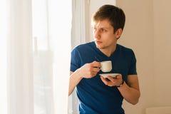 Man som dricker kaffe som ut ser fönstret Arkivfoto