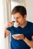 Man som dricker kaffe som ut ser fönstret Arkivbild