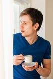 Man som dricker kaffe som ut ser fönstret Arkivfoton