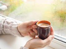 Man som dricker kaffe vid fönstret arkivfoton