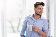 Man som dricker koppen kaffe nära fönster Arkivfoton
