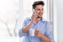 Man som dricker koppen kaffe nära fönster Arkivfoto