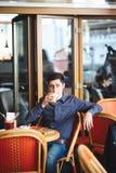 Man som dricker stor latte på en kafétabell royaltyfri foto