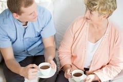 Man som dricker te med den mogna kvinnan Arkivfoton