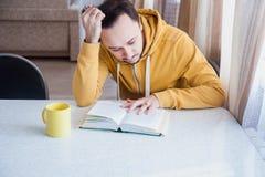 Man som dricker te och läsning en bok Arkivfoton