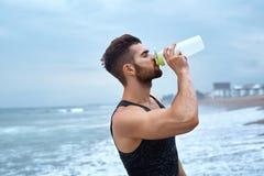 Man som dricker uppfriskande vatten efter genomkörare på stranden drink royaltyfri fotografi