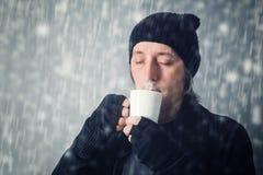 Man som dricker varmt te Arkivfoton